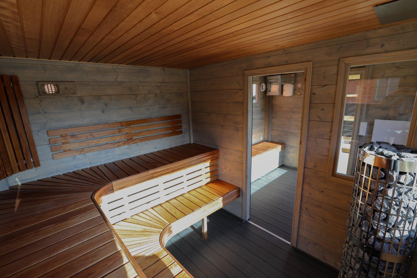 Bastuflotte invändig interiör med gråa väggar och lavar i värmebehandlad asp