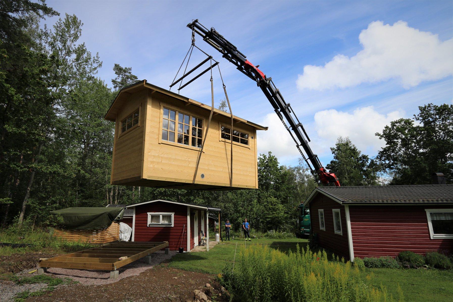 Kranbil med 22 meter lång arm för att lyfta stugan