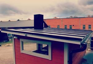 Snyggt lutande tak på gårdsbastu i bandplåt